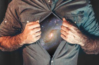 Un homme écarte sa chemise, sur sa poitrine apparait l'univers.