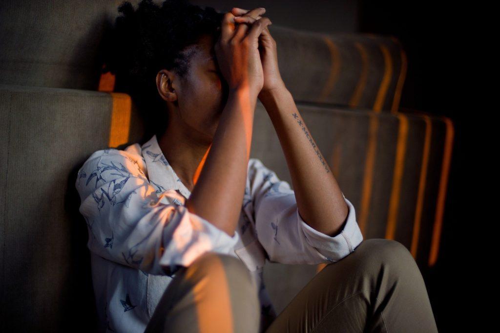 Une femme est assise les coudes sur les genoux et la tête dans les mains. Pour illustrer que l'on ne reçoit pas toujours ce que l'on a demandé.